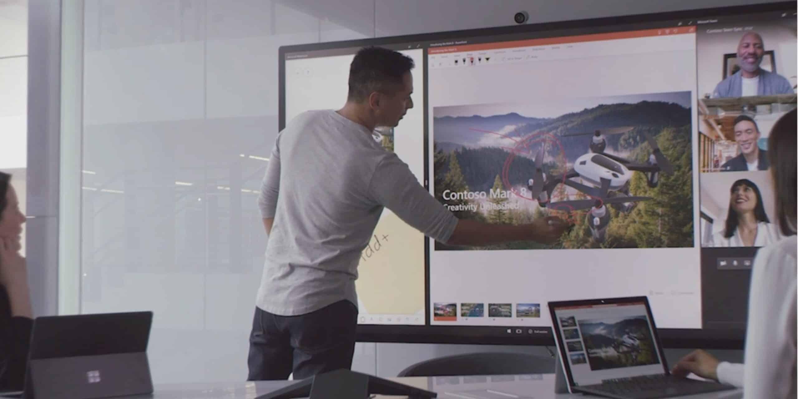 Microsoft Surface Hub 2S Whiteboard, Mann schreibt auf dem Whiteboard und nimmt gerade an einer Videokonferenz teil